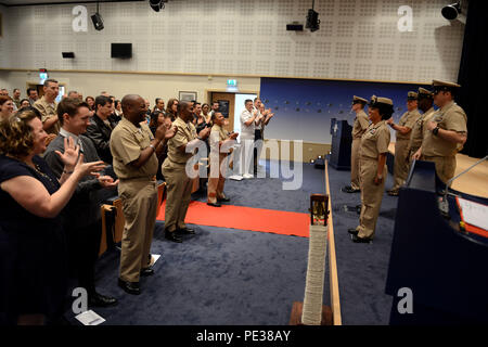 150916-N-XG305-400 BRUSSELS (Sept 16, 2015) - Family and friends applaud three newly frocked chief petty officers during a pinning ceremony at NATO headquarters in Brussels, Belgium. Three chief petty officers received their collar devices after completing the chief petty officer indoctrination. (U.S. Navy photo by Mass Communication Specialist 1st Class Mel Orr/RELEASED) - Stock Photo