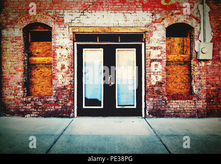 A close up of double doors on a colorful old brick storefront being restored with large window sills. - Stock Photo