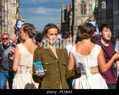 Pretty female Fringe performers in World War II costume of Dear Lucy show handing out flyers, Royal Mile, Edinburgh, Scotland, UK during festival - Stock Photo