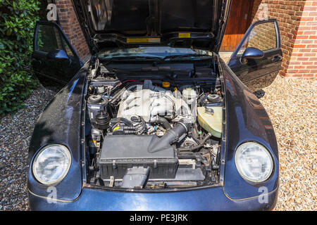 Open bonnet (hood) of a vintage Porsche 968 and the 3 litre straight-four engine (Front longitudinal inline four cylinder water cooled 16v VarioCam) - Stock Photo