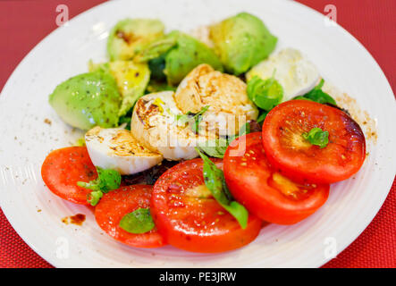 Healthy lifestyle: typical Mediterranean diet, tricolore salad ingredients sliced red tomatoes, white buffalo mozzarella cheese and green avocado pear - Stock Photo