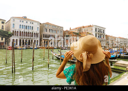 Young woman with green dress holding her hat when looking to Venice Grand Canal. Back view of traveler girl in Venice, Italy. - Stock Photo