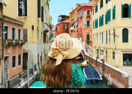 Back view of young woman with straw hat looking at Venice colorful buildings from a bridge on canal, Venice, Italy - Stock Photo