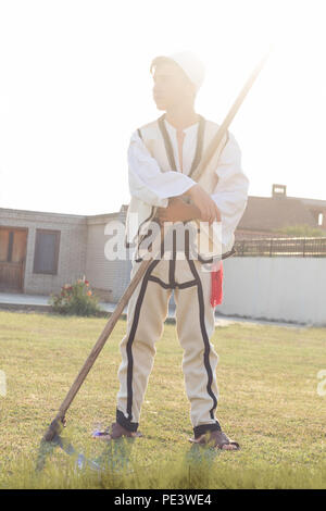 young man in traditional costume mow the grass with scythe in the old way - Stock Photo
