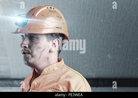 portrait of tired rail worker with orange unifom and helmet light in front of tunnel - Stock Photo