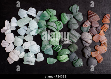 bottle necks glass pieces polished by the sea on black background - Stock Photo