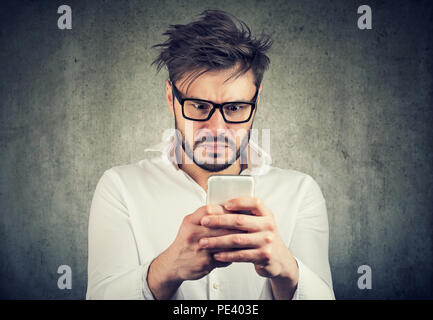 stunned man, surprised offended, shocked by what he sees on his smartphone - Stock Photo