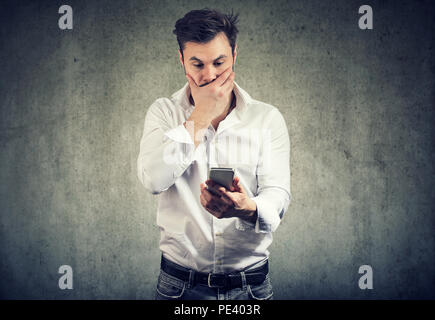 Young stylish man covering mouth in stress and astonishment while watching smartphone standing on gray background - Stock Photo