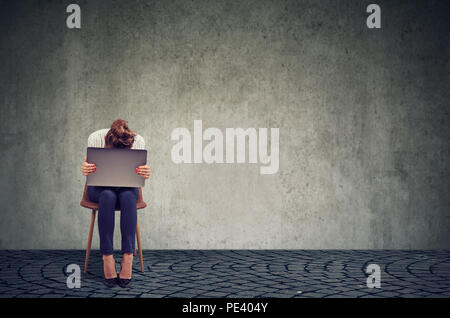 Anonymous woman sitting on chair with laptop on knees and looking desperate in crisis against gray wall background - Stock Photo