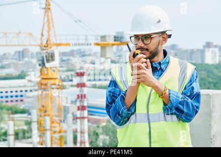 Construction engineer using radio - Stock Photo