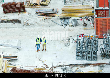 Building inspectors reading blueprint on construction site - Stock Photo