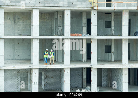 Construction engineers in unfinished building - Stock Photo