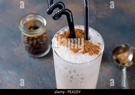 Milk chocolate cocktail or cold whipped coffee with milk and ice sprinkle cocoa on dark background, copy space, - Stock Photo