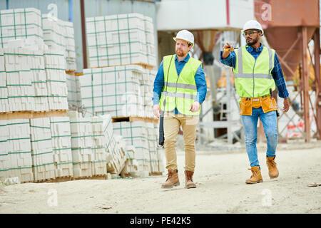 Building inspectors walking on construction site - Stock Photo