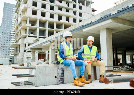Construction engineers resting and chatting - Stock Photo