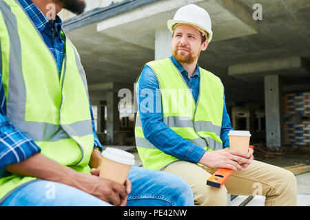 Construction engineer listening to colleague - Stock Photo