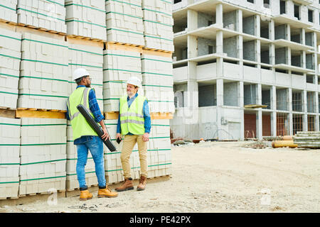 Construction engineers speaking near materials - Stock Photo