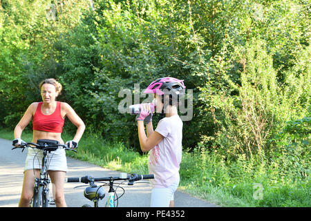 Little girl is refreshing with water on family biking on the road - Stock Photo