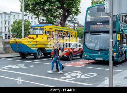 The Duck Tours amphibious vehicle waiting at a pedestrian crossing with a car and bus in the centre of Dublin Ireland - Stock Photo