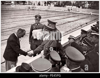1936 NAZI OLYMPICS Adolf Hitler shakes hands with an Olympic swimming pool official during the 1936 Nazi Germany Olympics in Berlin: - Stock Photo