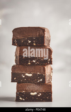 Stack of chocolate fudge bars on white background. Clean eating concept. Raw vegan dessrt. - Stock Photo