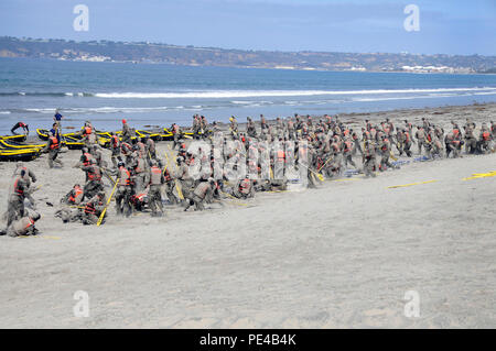 CORONADO, Calif. (Sept. 2, 2015) Basic Underwater Demolition/SEAL (BUDS) candidates cover themselves in sand during surf passage on Naval Amphibious Base Coronado. Surf passage is one of the many physically demanding evolutions that are a part of the first phase of SEAL training. (U.S. Navy photo by Mass Communication Specialist 1st Class Michael Russell/Released) - Stock Photo