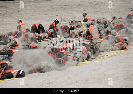 CORONADO, Calif. (Sept. 2, 2015) Basic Underwater Demolition/SEAL (BUDS) candidates cover themselves in sand during surf passage on Naval Amphibious Base Coronado. Surf passage is one of the many physically-demanding evolutions that are a part of the first phase of SEAL training. (U.S. Navy photo by Mass Communication Specialist 1st Class Michael Russell/Released) - Stock Photo