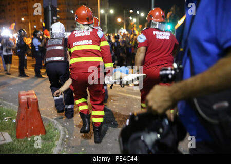 Bucharest, Romania - August 10, 2018: Paramedics are offering first aid to an injured football supporter by tear gas receives during the violent anti- - Stock Photo
