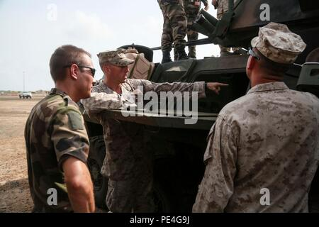 CAMP LEMONNIER, Djibouti (Sept. 9, 2015) U.S. Marine Capt. Thomas Vallely, middle, explains the capabilities of a Light Armored Vehicle (LAV-25). Vallely is the company commander with Delta Company, 1st Light Armored Reconnaissance Detachment, Battalion Landing Team 3rd Battalion, 1st Marine Regiment, 15th Marine Expeditionary Unit. Elements of the 15th MEU are preparing to conduct bilateral training with the 5th Overseas Combined Arms Regiment (RIAOM) in Djibouti in order to improve interoperability between the MEU and the French military. (U.S. Marine Corps photo by Sgt. Steve H. Lopez/Relea - Stock Photo