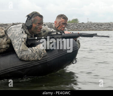 New York Army National Guard Sgt. 1st Class David Ditullio and Sgt. John Krupa, both infantrymen with Troop C, 2nd Squadron,101st Cavalry Regiment, stand watch at the bow of a F470 Combat Rubber Raiding Craft during a training exercise in Buffalo, N.Y, Sept. 13, 2015. For the exercise, Soldiers from Troop C practiced covertly deploying from an F470 Combat Rubber Raiding Craft and establishing a presence on a simulated enemy beachhead. - Stock Photo