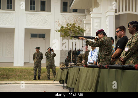 Maj. Gen. Dato' Mohd Suhaimi bin Hj Mohd Zuki, commanding general of the Malaysian Army Training and Doctrine Command, prepares to fire an M500A1 shotgun during Non-lethal Weapons Executive Seminar, Sept. 16, 2015. Senior military members received the chance to fire weapons used by instructors during the exercise after the final demonstration. NOLES is an annual exercise hosted by U.S. Marine Corps Forces, Pacific and is the U.S. Pacific Command's premier multilateral theater security cooperation event for non-lethal weapons. Non-lethal weapons and tactics provide options for U.S. Marines and  - Stock Photo