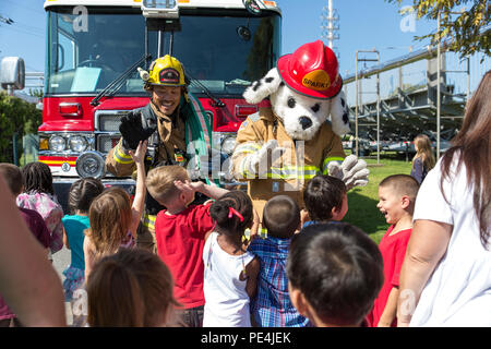 Students with Matthew C. Perry Elementary School gather around to greet Eiji Aridome, a firefighter aboard station, and, Sparky, the air station's fire safety dog, during M.C. Perry Elementary and High School's 9/11 Remembrance Walk aboard Marine Corps Air Station Iwakuni, Japan, Sept. 11, 2015. Beginning at 9:11 a.m., this is the third annual walk hosted by the schools and an event that helps students understand the significance of never forgetting, according to Devin Johnston-Lee, fire chief for the air station. (U.S. Marine Corps photo by Sgt. Antonio J. Rubio/Released) - Stock Photo
