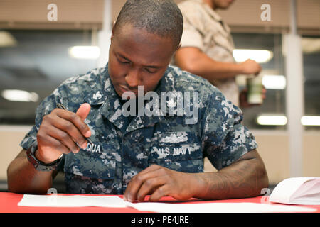 Petty Officer 2nd Class, Stephen Fuqua, culinary specialist, Robert E. Bush Naval Hospital, takes a test on proper culinary safety procedures during the Chef of the Quarter Competition aboard the Combat Center, Sept. 15, 2015. (Official Marine Corps photo by Lance Cpl. Levi Schultz/Released) - Stock Photo