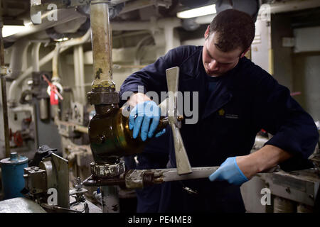 150918-N-ZZ999-020  ATLANTIC OCEAN (Sept. 18, 2015) - Machinist's Mate Fireman Kyle Wood replaces a hydraulic valve below the aircraft elevator on the aircraft carrier USS Dwight D. Eisenhower (CVN 69). Dwight D. Eisenhower is underway conducting carrier qualifications. (U.S. Navy photo by Mass Communication Specialist Seaman Apprentice Liam N. Antinori/Released) - Stock Photo