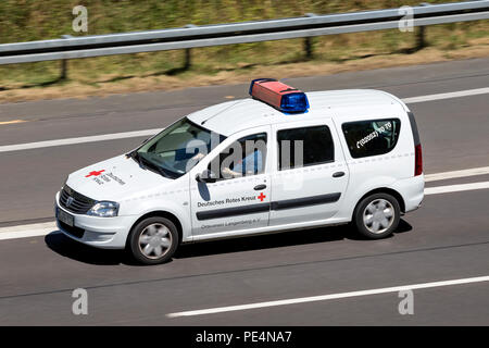 Dacia Logan of the German Red Cross on motorway. The German Red Cross, or the DRK, is the national Red Cross Society in Germany. - Stock Photo