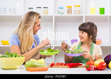 Happy mother and her daughter enjoy making and having healthy meal together at their home. - Stock Photo