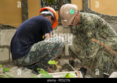 A Philippine sailor and U.S. Navy Seabee Petty Officer 3rd Class Anthony Carreno, steel worker, 9th Engineer Support Battalion, 3d Marine Logistics Group, build a wall as part of the humanitarian civic assistance project at Concepcion Elementary School in Palawan, Philippines, during Amphibious Landing Exercise 2015 (PHIBLEX 15), Oct. 6. PHIBLEX 15 is an annual bilateral training exercise conducted with the Armed Forces of the Philippines in order to strengthen our interoperability and working relationships across a wide range of military operations from disaster relief to complex expeditionar - Stock Photo