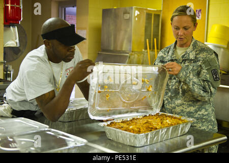 U.S. Army Sgt. Cynthia Dominguez, from the 1178th Forward Support Company, South Carolina Army National Guard, helps retired guardsman Bernard Sherman with dinner for guardsmen staying at the Georgetown, S.C., armory during the flood response and recovery; the meal was generously donated by a local business, Oct. 9, 2015. The South Carolina National Guard has been activated to support state and county emergency management agencies and local first responders as historic flooding impacts counties statewide. Currently, more than 2,900 South Carolina National Guard members have been activated in r - Stock Photo