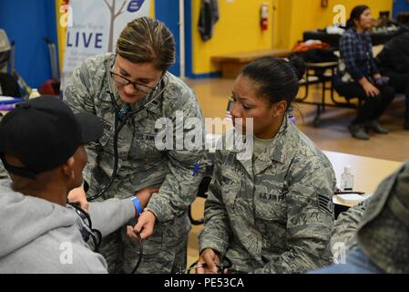First Lt. Sara Kucharski and Staff Sgt. Stefany Jones, 108th Medical Group, New Jersey Air National Guard, check the blood pressure of a homeless veteran at the New Jersey Department of Military and Veterans Affairs Stand Down Day at the John F. Kennedy Recreation Center in Newark, N.J., on Oct. 10, 2015. The stand down day allows the veterans to get much-needed care and services from a wide array of state agencies and nonprofit organizations. Members of the 108th Medical Group have been providing care at stand down days for more than 10 years and were providing blood pressure checks as a mean - Stock Photo
