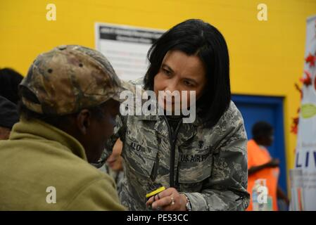 Lt. Col. Mauricia Alo, 108th Medical Group, New Jersey Air National Guard, checks the blood pressure of a homeless veteran at the New Jersey Department of Military and Veterans Affairs Stand Down Day at the John F. Kennedy Recreation Center in Newark, N.J., on Oct. 10, 2015. The stand down day allows the veterans to get much-needed care and services from a wide array of state agencies and nonprofit organizations. Members of the 108th Medical Group have been providing care at stand down days for more than 10 years and were providing blood pressure checks as a means to have conversations with th - Stock Photo