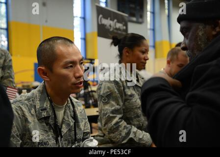 First Lt. Stan Pang, 108th Medical Group, New Jersey Air National Guard, checks the blood pressure of a homeless veteran at the New Jersey Department of Military and Veterans Affairs Stand Down Day at the John F. Kennedy Recreation Center in Newark, N.J., on Oct. 10, 2015. The stand down day allows the veterans to get much-needed care and services from a wide array of state agencies and nonprofit organizations. Members of the 108th Medical Group have been providing care at stand down days for more than 10 years and were providing blood pressure checks as a means to have conversations with the  - Stock Photo