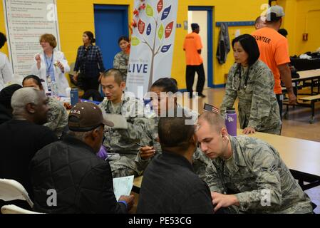Members of the 108th Medical Group, New Jersey Air National Guard, provide blood pressure checks to homeless veterans at the New Jersey Department of Military and Veterans Affairs Stand Down Day at the John F. Kennedy Recreation Center in Newark, N.J., on Oct. 10, 2015. The stand down day allows the veterans to get much-needed care and services from a wide array of state agencies and nonprofit organizations. Members of the 108th Medical Group have been providing care at stand down days for more than 10 years and were providing blood pressure checks as a means to have conversations with the vet - Stock Photo