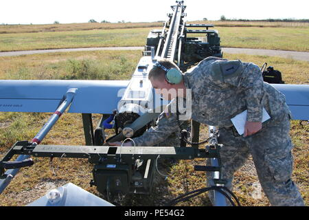 Spc. Kyle Smith, an unmanned aircraft systems repairer with Company D, 1st Engineer Battalion, 1st Armored Brigade Combat Team, 1st Infantry Division, prepares to start the RQ7-B Shadow unmanned aerial system Sept. 30 at Fort Riley, Kan. Soldiers from the 1st ABCT, 1st Inf. Div., launched the UAS along an approved air corridor and flew it back utilizing national airspace. Fort Riley was the first installation to receive permission from the FAA to fly a UAS into national airspace. - Stock Photo