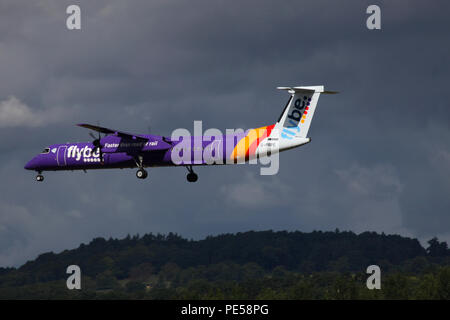 with dark clouds in the background flybe De Havilland DHC-8-400 Dash 8 plane G-PRPE makes its final approach into Edinburgh airport - Stock Photo