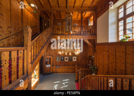 Splendid, wood-paneled entrance hall with chandelier and red carpet of the mountain lodge 'Berliner Hütte' in the Zillertal, Austria - Stock Photo