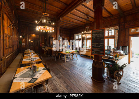 A splendid dining room with high wood ceiling and wood-paneled walls in the landmarked Berliner Hütte at Zillertal, Austria - Stock Photo