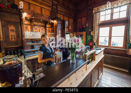 Blonde woman with braid behind the bar counter in the splendid dining room of the mountain hut Berliner Hütte smiles at the camera, Zillertal, Austria - Stock Photo