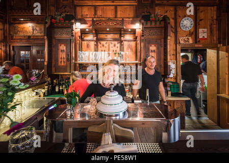 Blonde woman and man behind the bar counter in the splendid dining room of the mountain hut Berliner Hütte smile at the camera, Zillertal, Austria - Stock Photo