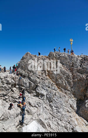 Tourists climbing to the Golden Cross - the highest point in Germany on the summit of Zugspitze at 2,962 m above sea level - Stock Photo