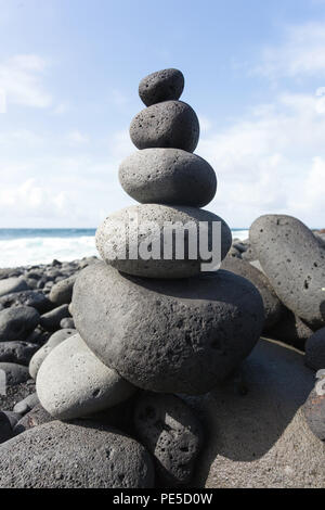 Stacked stones or pebbles on a beach with the blue sky in the background. - Stock Photo